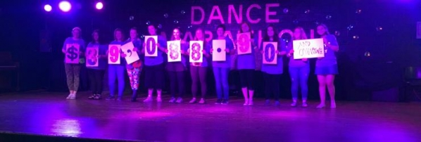 Dance marathon participants holding signs showing $39,088.90 raised
